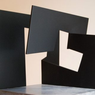 "<em>Jorge Oteiza: Construcción vacía con unidades planas positivo negativo</em><br>Steel painted black on stone base · 27,5 x 38,5 x 29 cm. Two ítems · enrolled in sculpture ""TZA"" and in the base with metal pointer ""PARA EL GRANDE Y ENTRAÑABLE José Luis con OTEITZA"" · Made in 1992 - 1996 as a version of one of 60&#039;s - 70&#039;s"